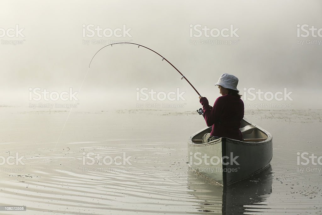 Outdoors girl catching fish from canoe on misty morning lake royalty-free stock photo