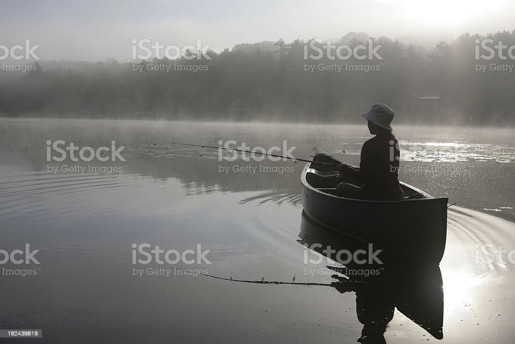 Outdoors girl fishing from canoe on lake in misty sunrise stock photo