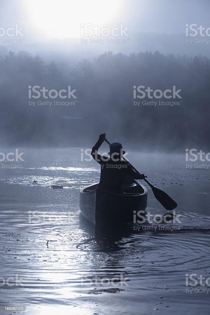Outdoors girl paddling canoe on lake in blue misty sunrise stock photo