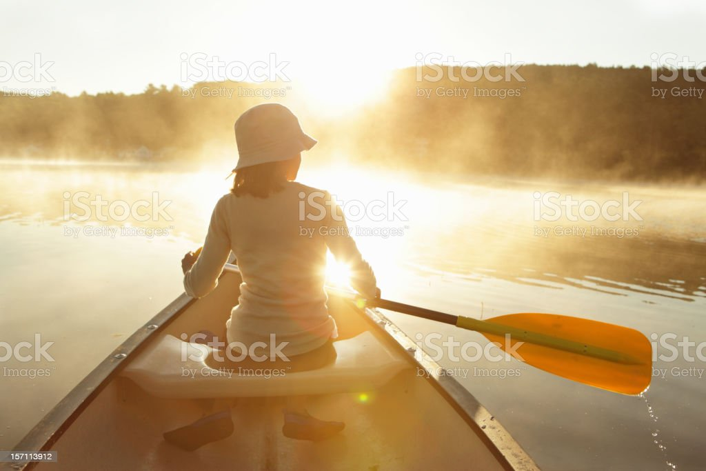 Outdoors girl paddling canoe on lake in bright misty sunrise stock photo