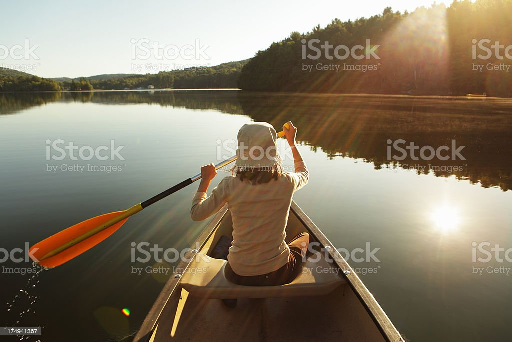 Outdoors girl paddling canoe on lake in bright misty sunrise stock photo