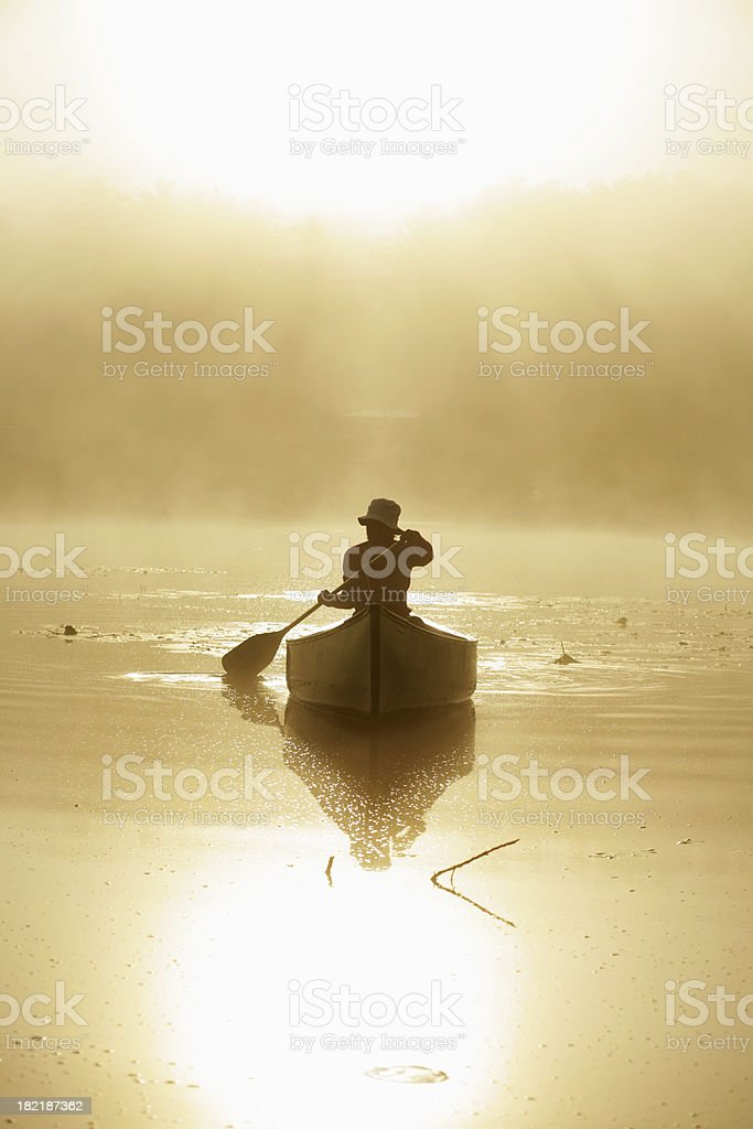Outdoors girl paddling canoe on lake in misty sunrise backlit stock photo