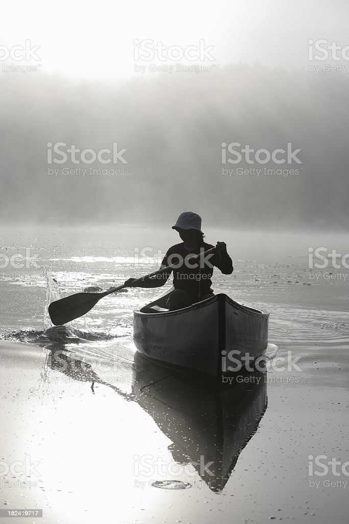 Outdoors girl paddling canoe on lake in misty sunrise backlit royalty-free stock photo