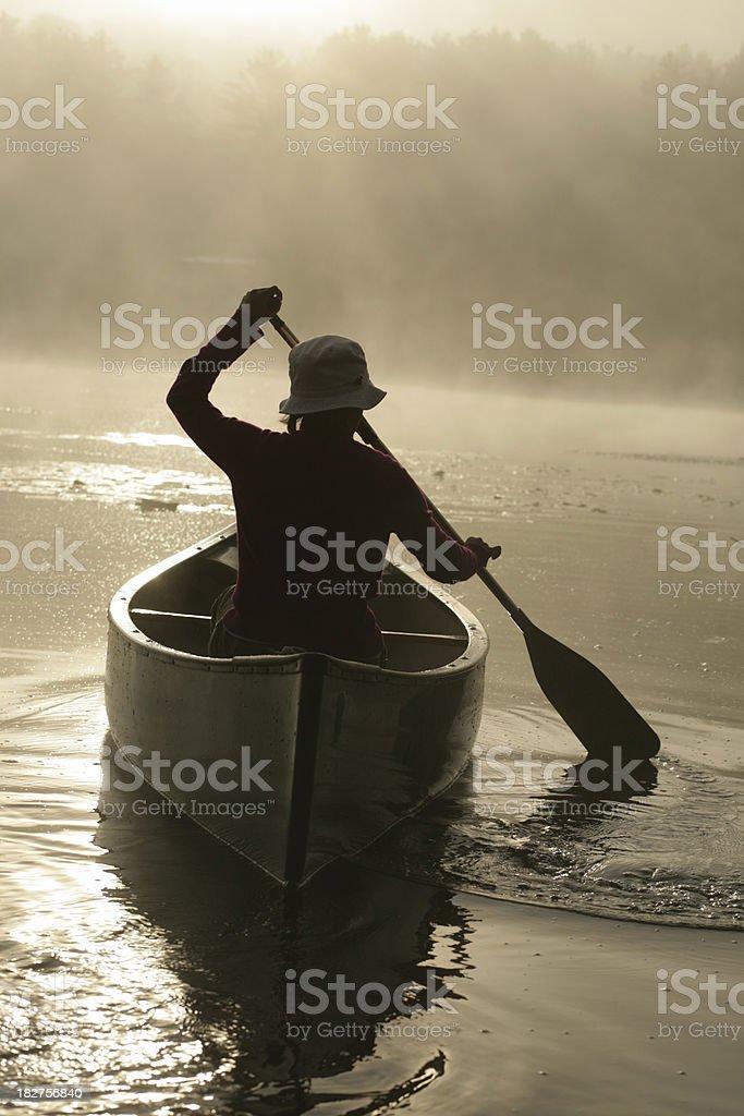 Outdoors girl paddling canoe on lake in misty sunrise backlit royalty-free stock photo