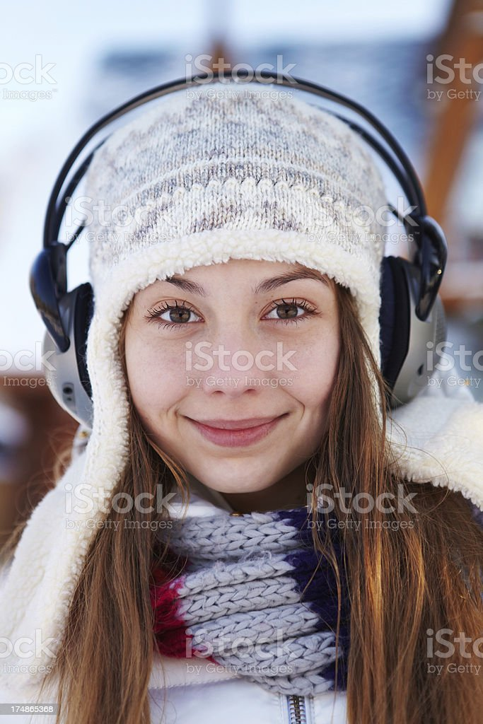 Outdoors on a winter day. Girl listen music. royalty-free stock photo