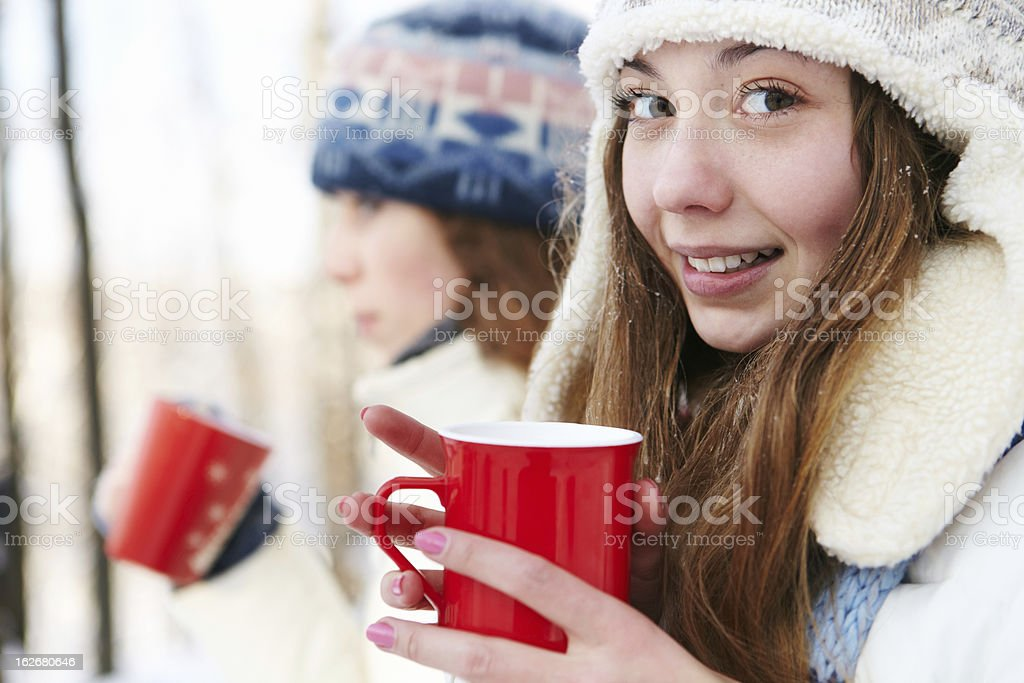 Outdoors on a winter day. Girls drink tea. royalty-free stock photo