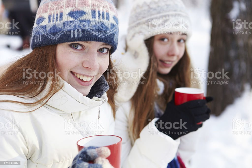 Outdoors on a winter day. Girls drink tea royalty-free stock photo