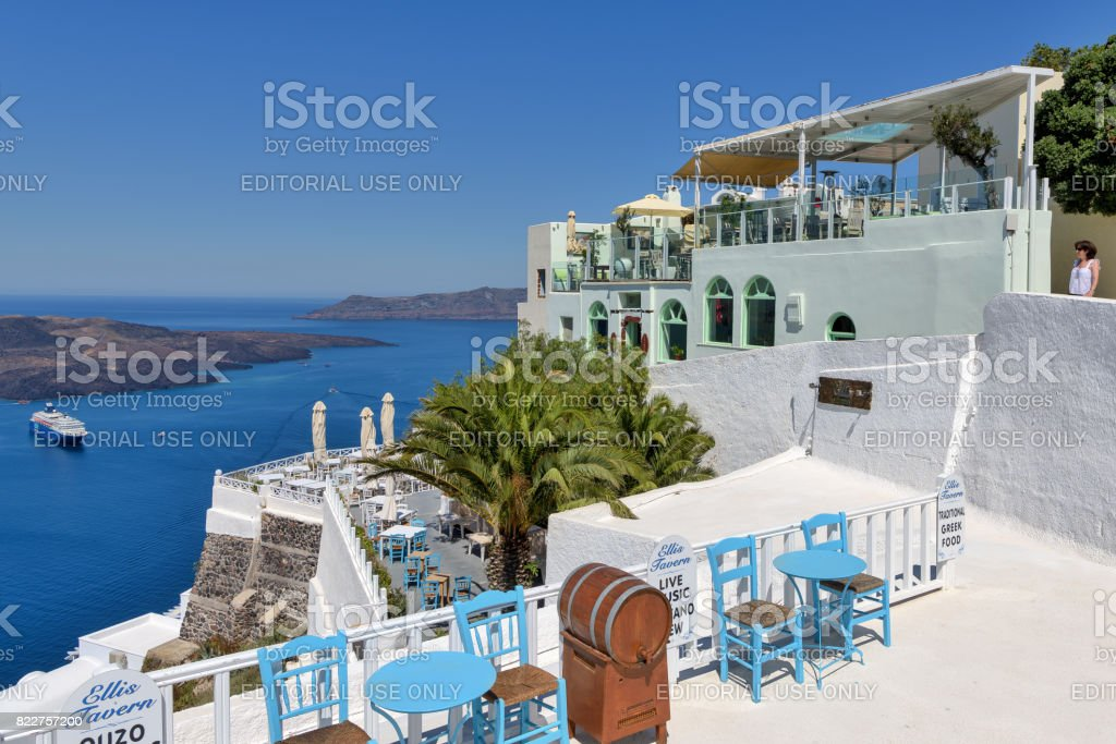Outdoors patio bar in the island of Santorini offers views of nearby Greek islands and Aegean sea. stock photo