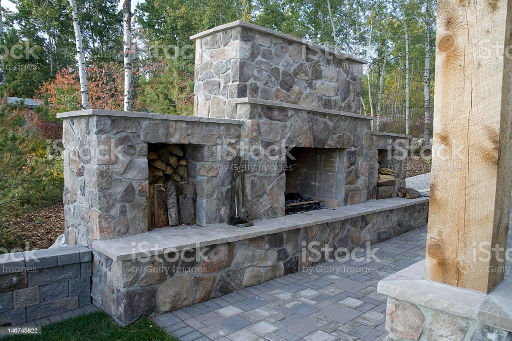 Outdoors stone fireplace with space for storing firewood stock photo