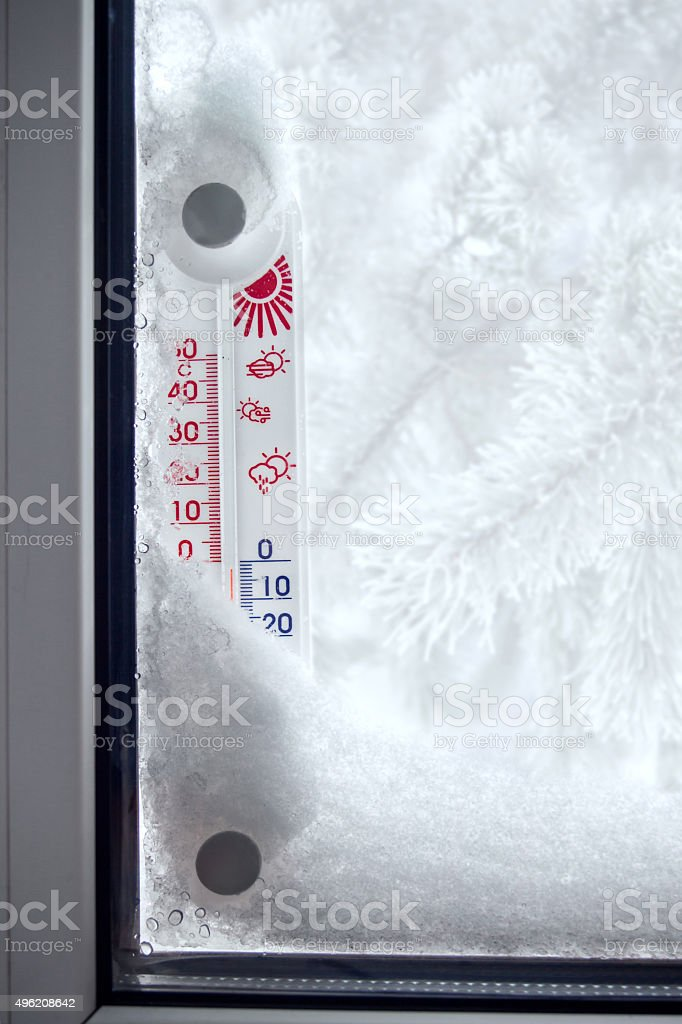 Outer thermometer on a frozen window stock photo