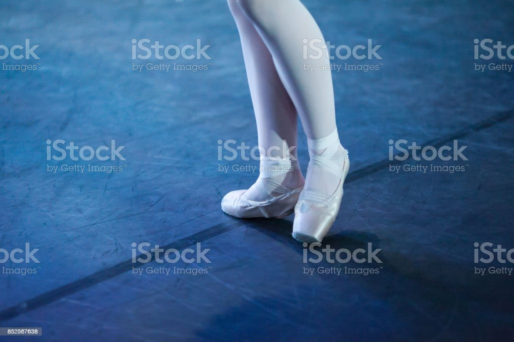 outfit, accessories, ballet concept. light pink pointe shoes has special form for unique feet of girl and two wight ribbons wrap around her ankles in opposite directions stock photo