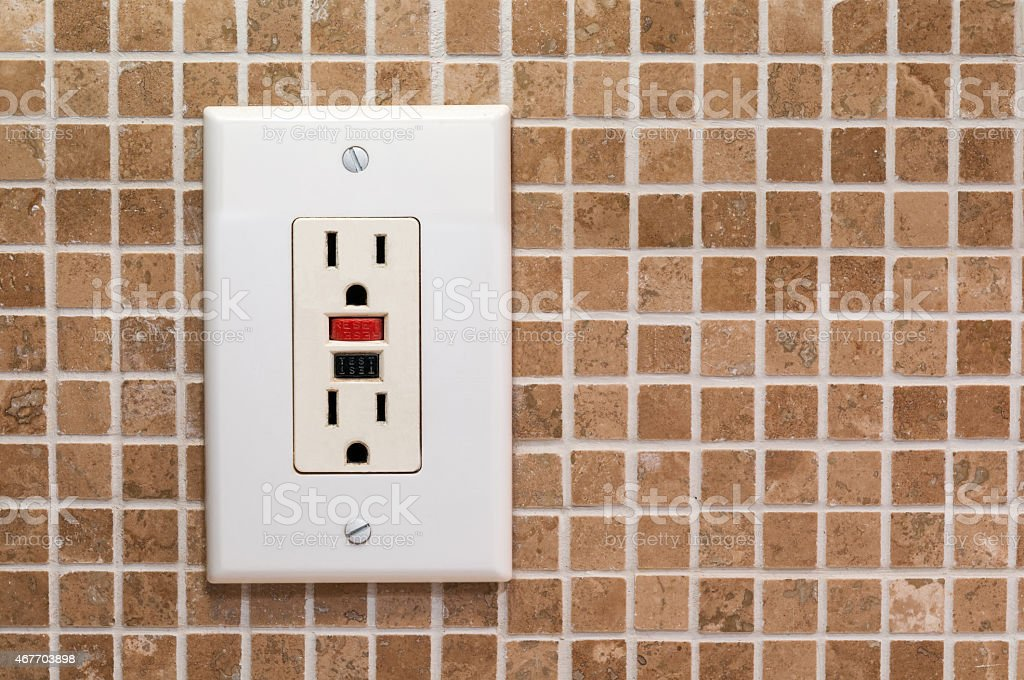 AC outlet on brown grouted tile wall stock photo