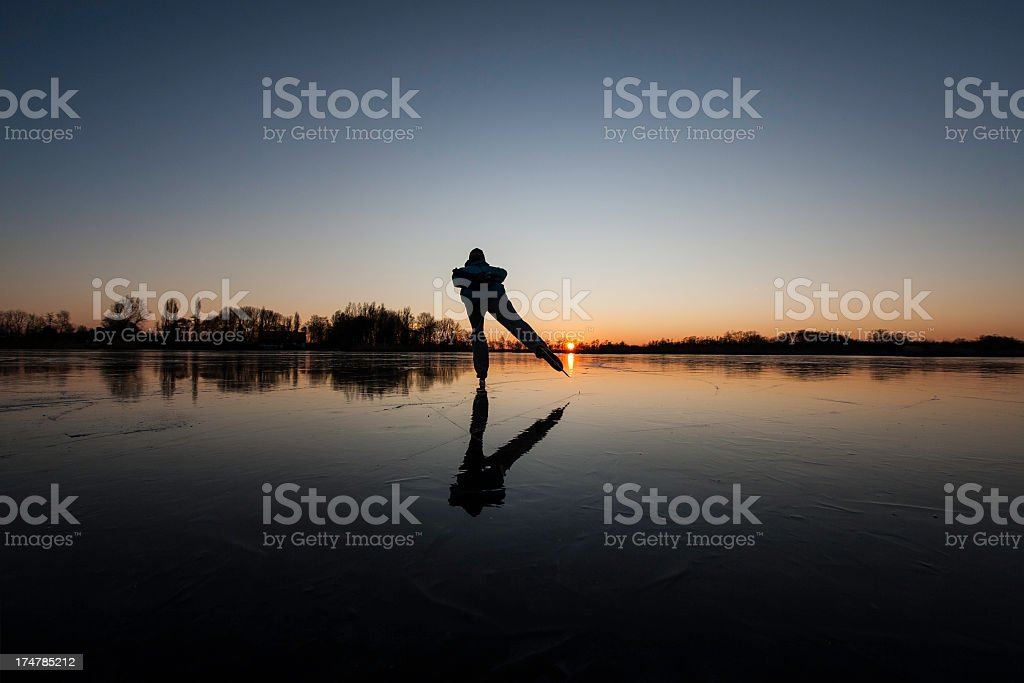 Outline of a person ice skating at dusk with gradient sky stock photo