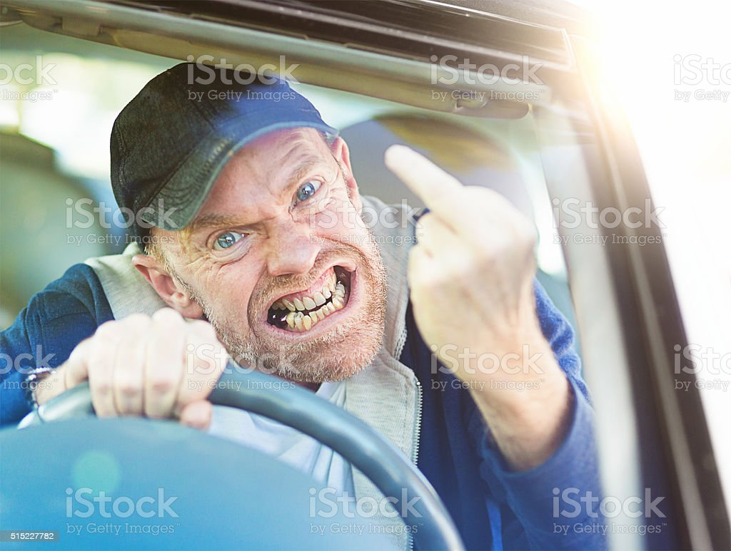 Out-of-control, grimacing male driver giving furious middle-finger gesture though windscreen stock photo