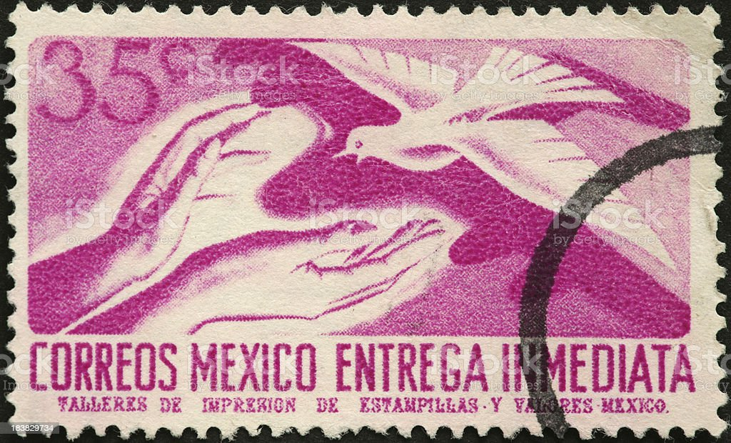 outreaching hands and white dove on Mexican stamp stock photo