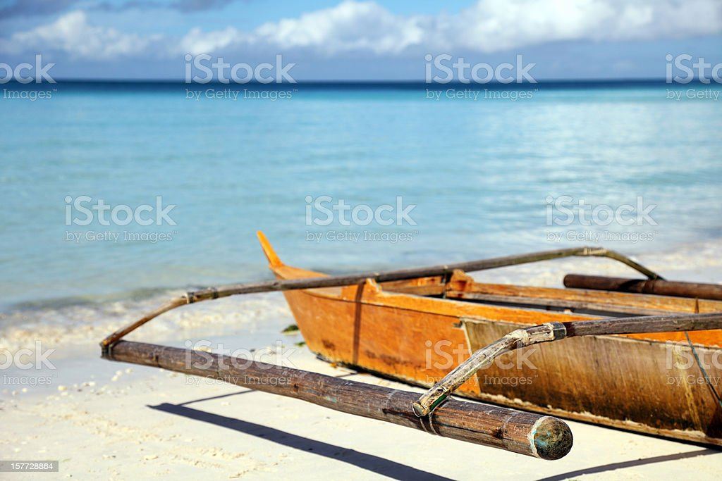 Outrigger boat on white sandy beach royalty-free stock photo