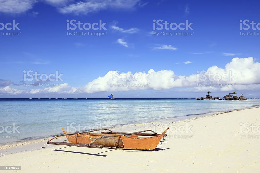 Outrigger boat stranded on the beach royalty-free stock photo