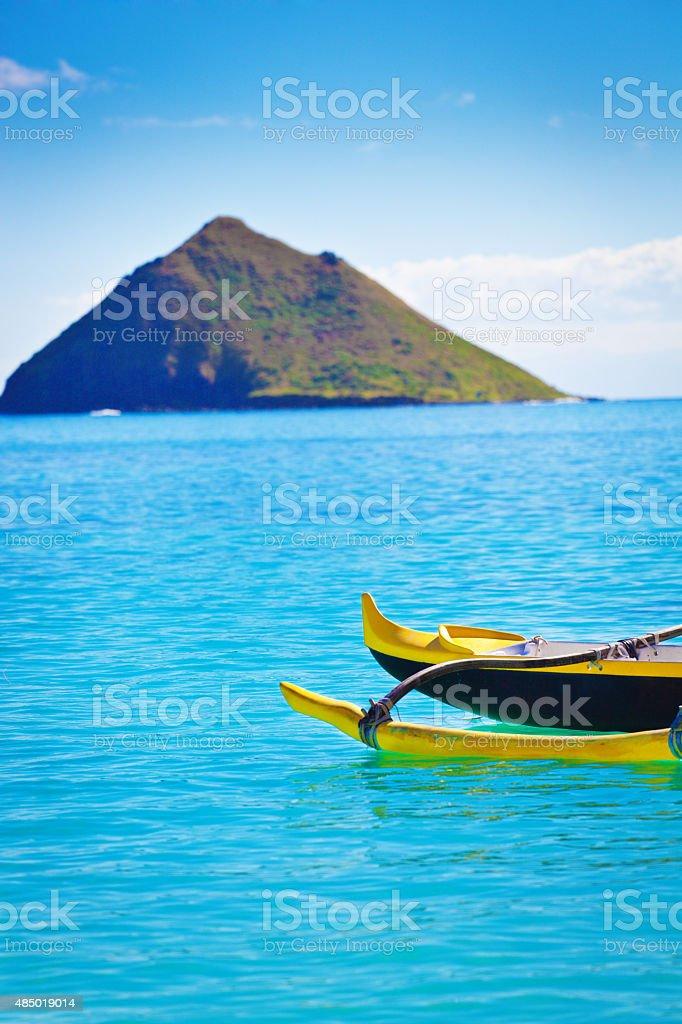 Outrigger Canoe off Lanikai Beach with Pacific Islands, Oahu, Hawaii stock photo