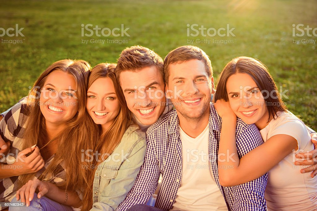 outside photo of happy smiling diverse five friends hugging stock photo