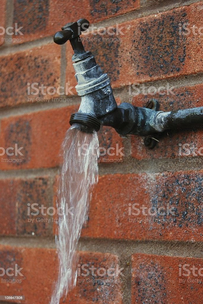 Outside tap with water gushing stock photo
