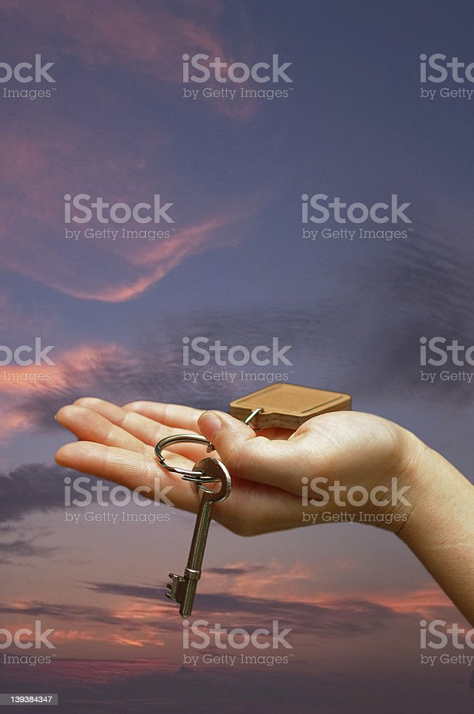 Outstretched palm holding a house key royalty-free stock photo