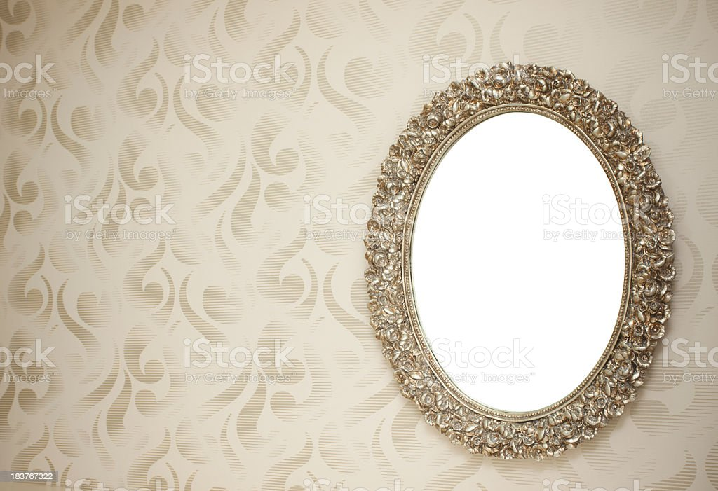 Oval mirror with vintage clipping path style frame on wall stock photo