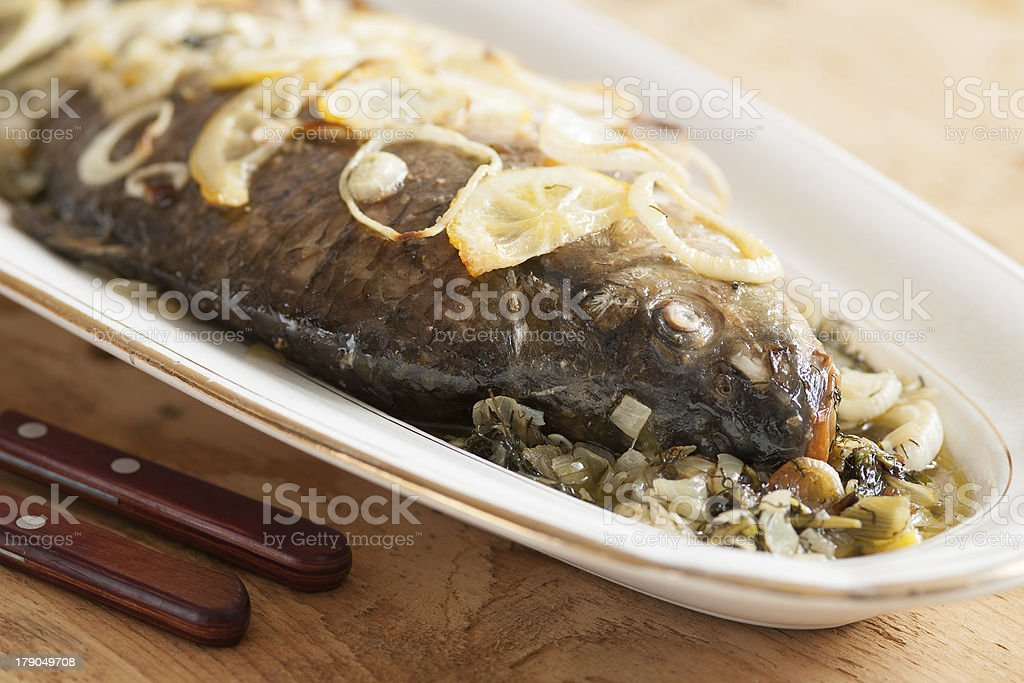 Oven baked carp fish with onions and lemon royalty-free stock photo