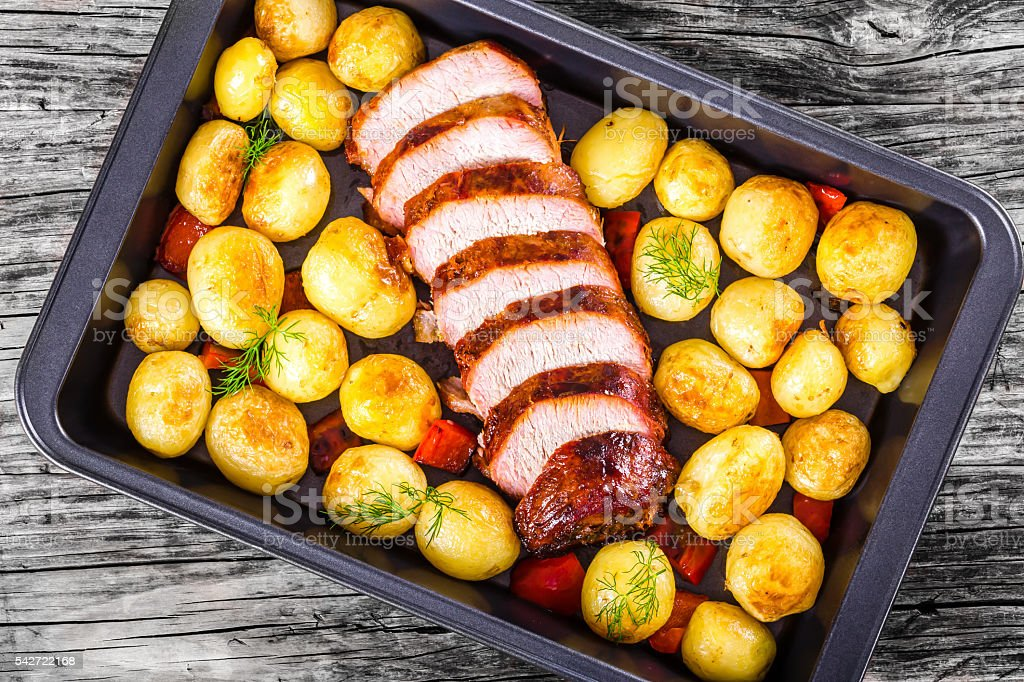 Oven Baked new potatoes with pork tenderloin stock photo