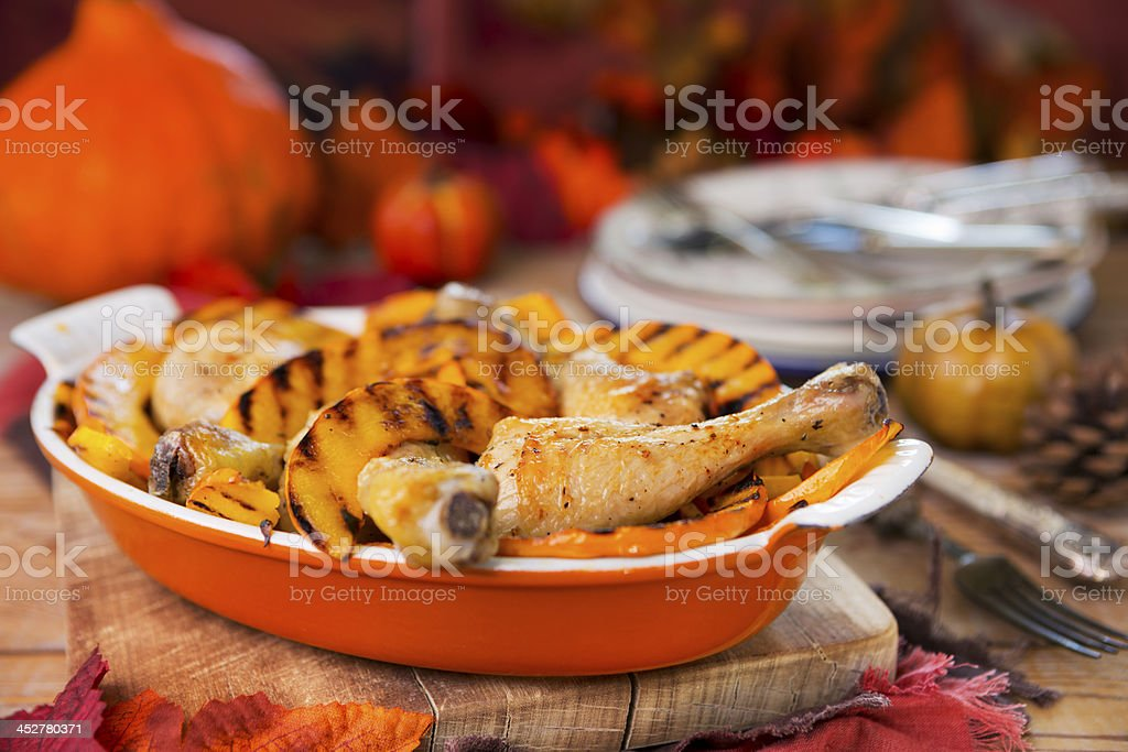 Oven roasted chicken with grilled pumpkin on a rustic table royalty-free stock photo