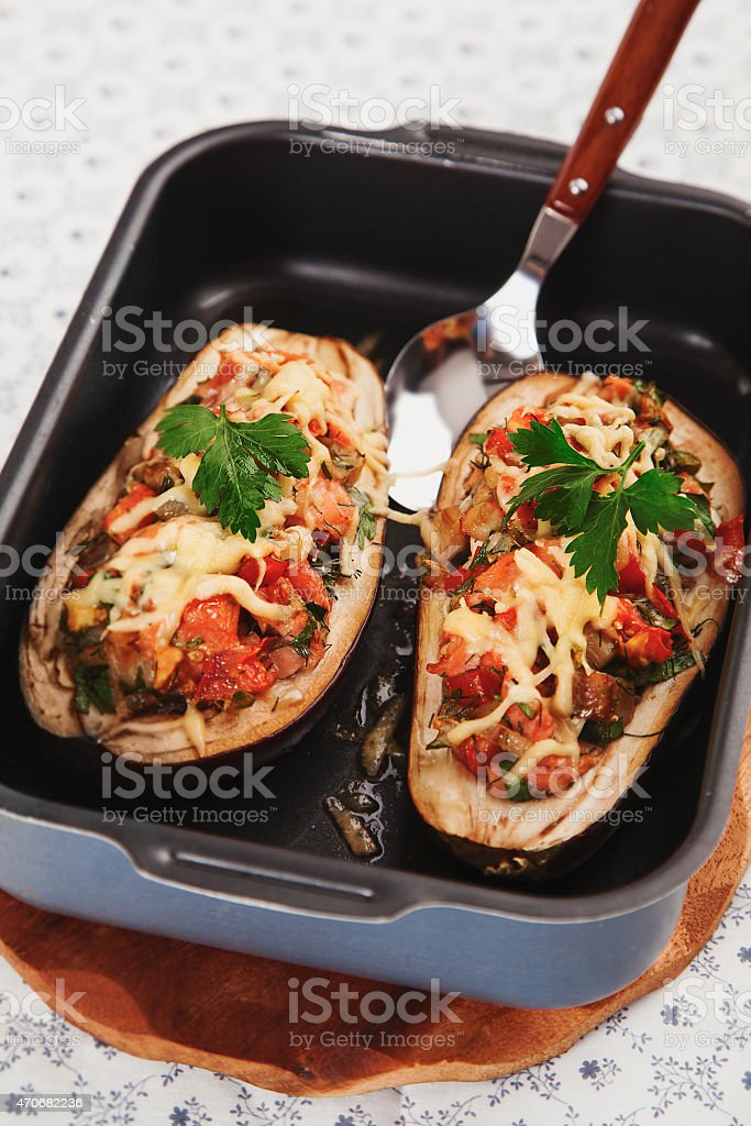 Oven tray containing two eggplants stuffed with vegetables stock photo