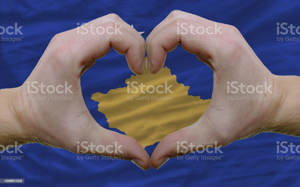 over flag of kosovo showed heart and love gesture stock photo