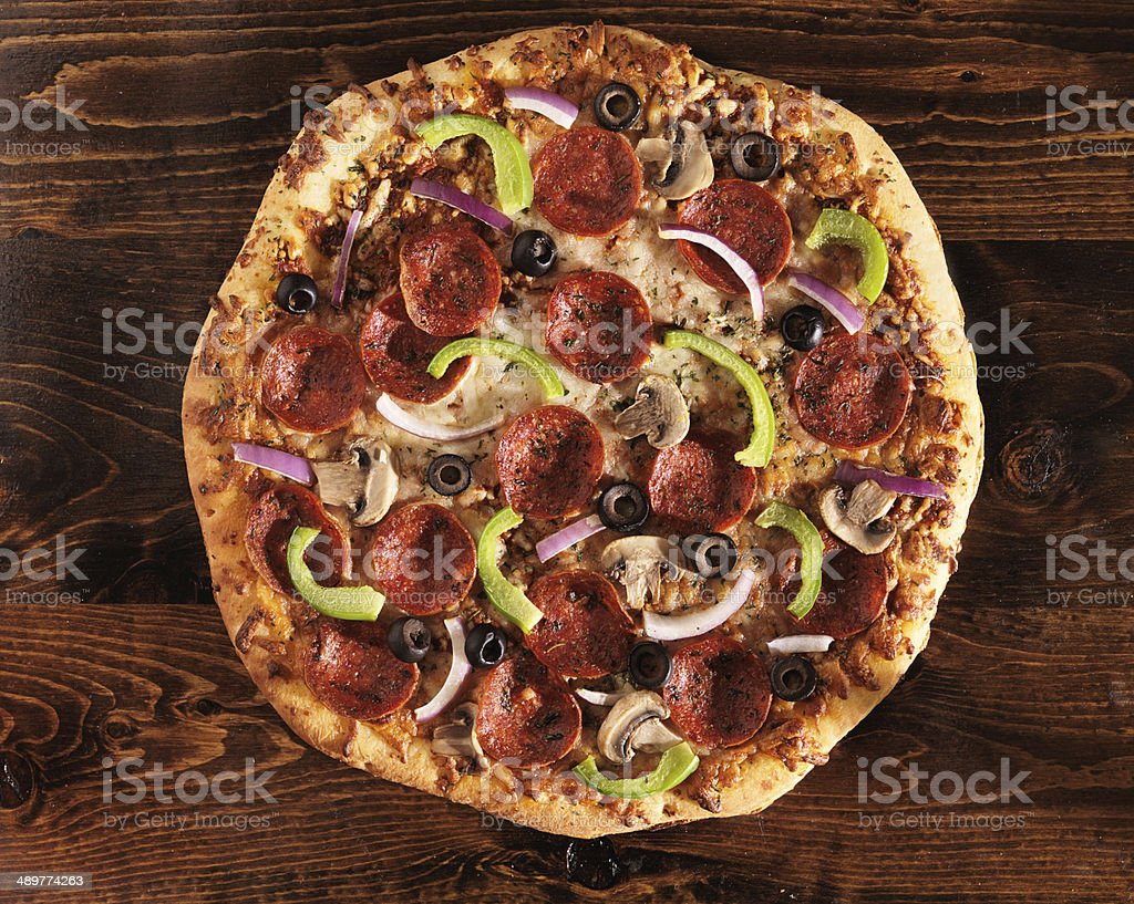 over head view of pizza with supreme toppings stock photo