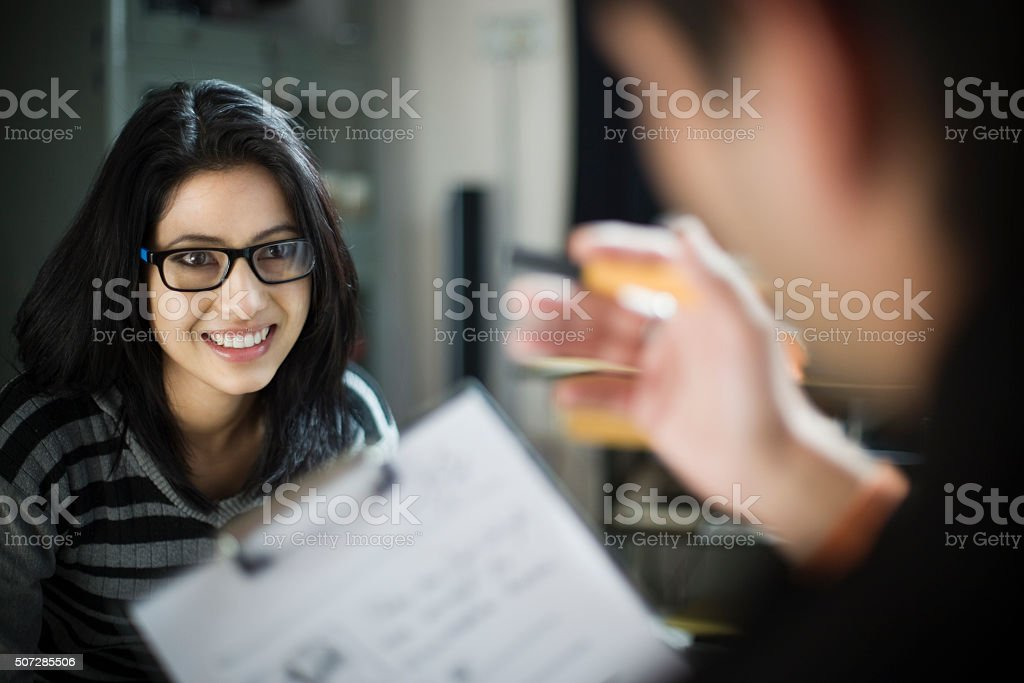 Over shoulder view of happy businesswoman listening to her colleague. stock photo