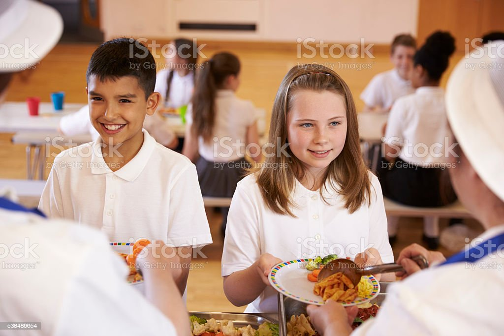 Over shoulder view of kids being served in school cafeteria stock photo
