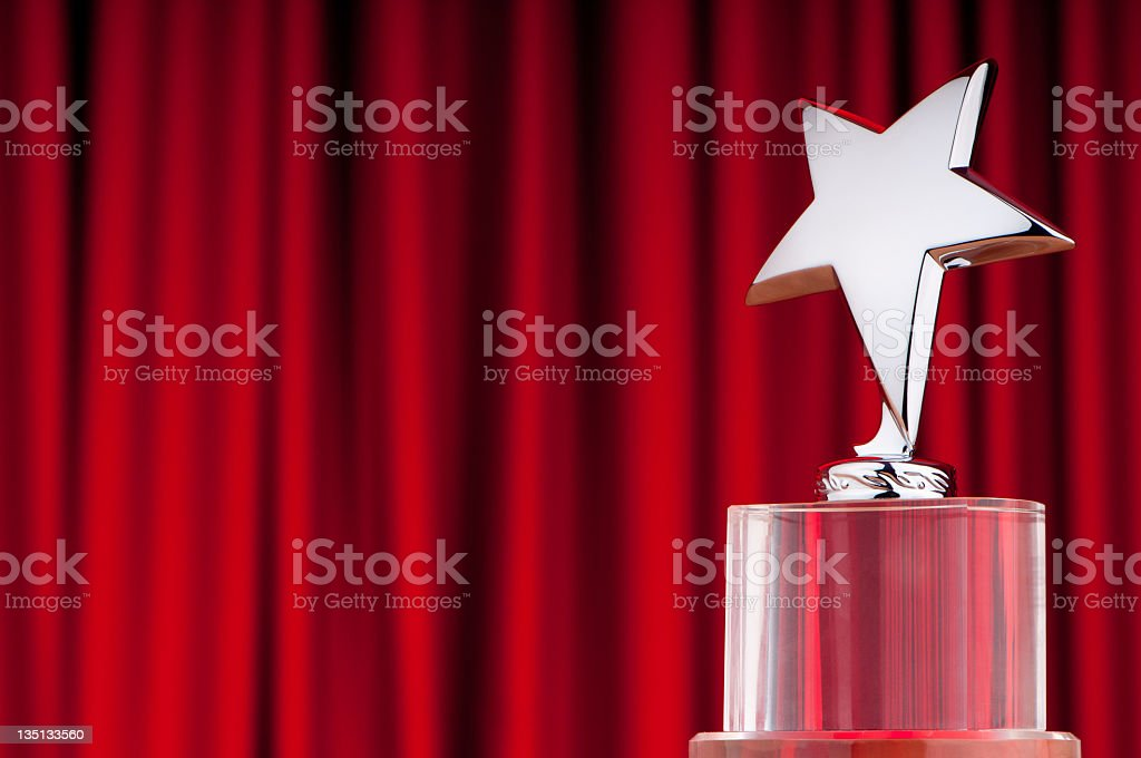 Over star award isolated on a red curtain backround stock photo