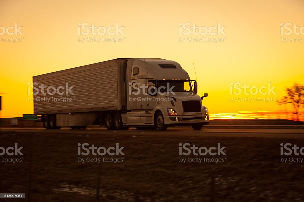 Over the road tractor trailer on the highway at sunrise. stock photo