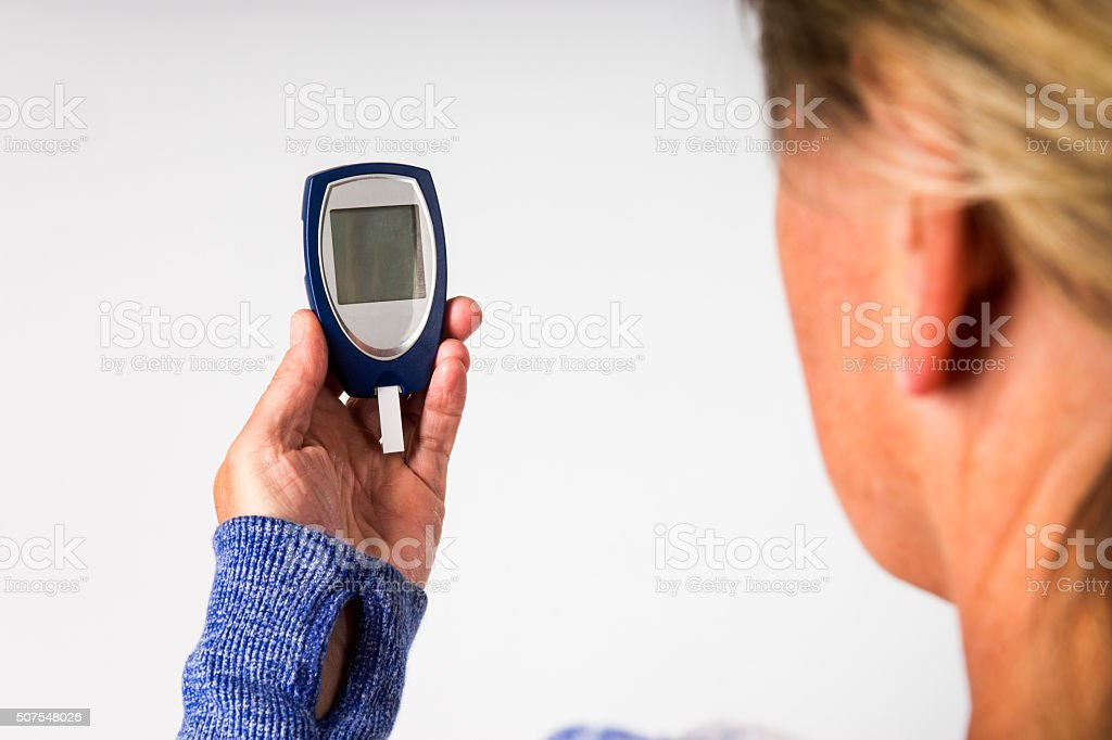Over the shoulder of a diabetes blood glucose meter. stock photo
