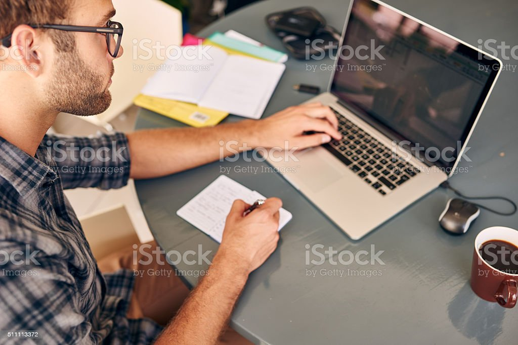 Over the shoulder shot of a young adult busy working stock photo