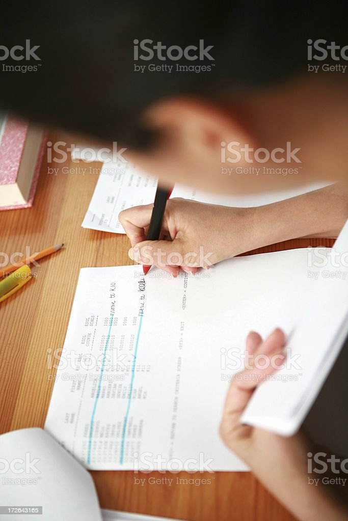 Over the shoulder shot of female working on papers stock photo
