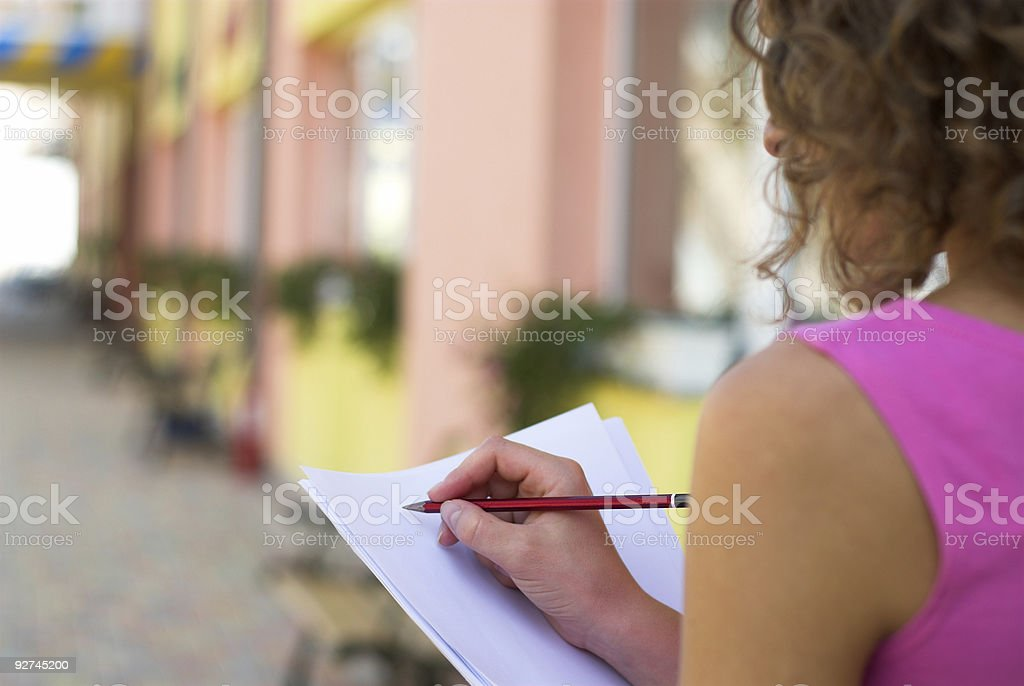 Over the shoulder view of a woman writing on paper royalty-free stock photo