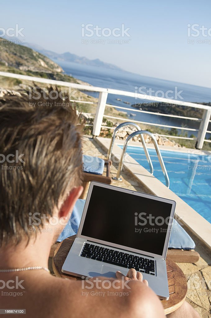 Over the Shoulder View of Poolside Laptop royalty-free stock photo