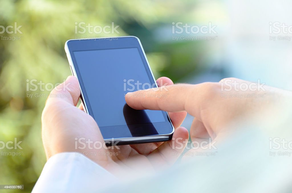 Over the shoulder view of young man using a smartphone stock photo