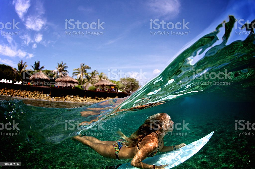 Over under duck dive of a surfer girl stock photo