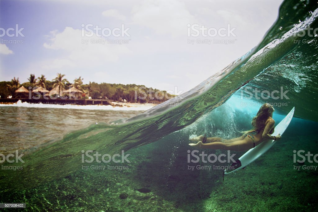 Over under duck dive photo of a surfer girl stock photo