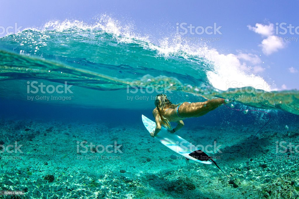Over under of girl duckdive an oncoming wave stock photo