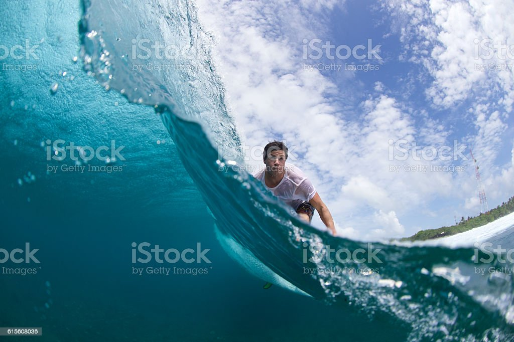 Over under split of a surfer on a wave stock photo