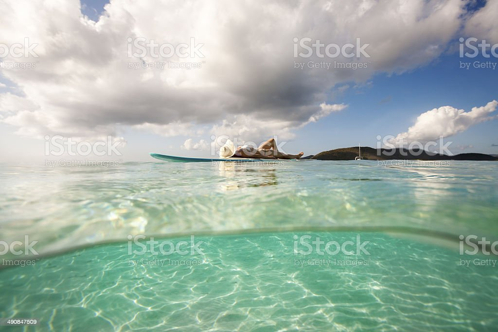 over under split shot of woman lying down on paddleboard stock photo