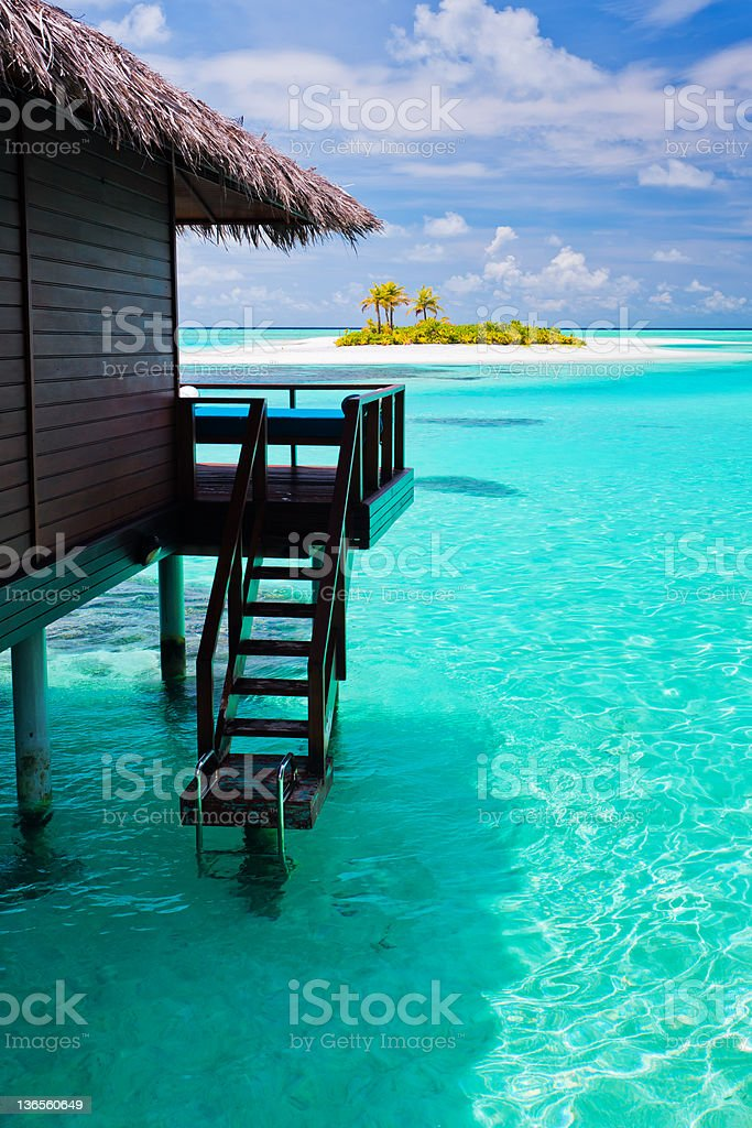 Over water bungalow with steps into blue lagoon royalty-free stock photo