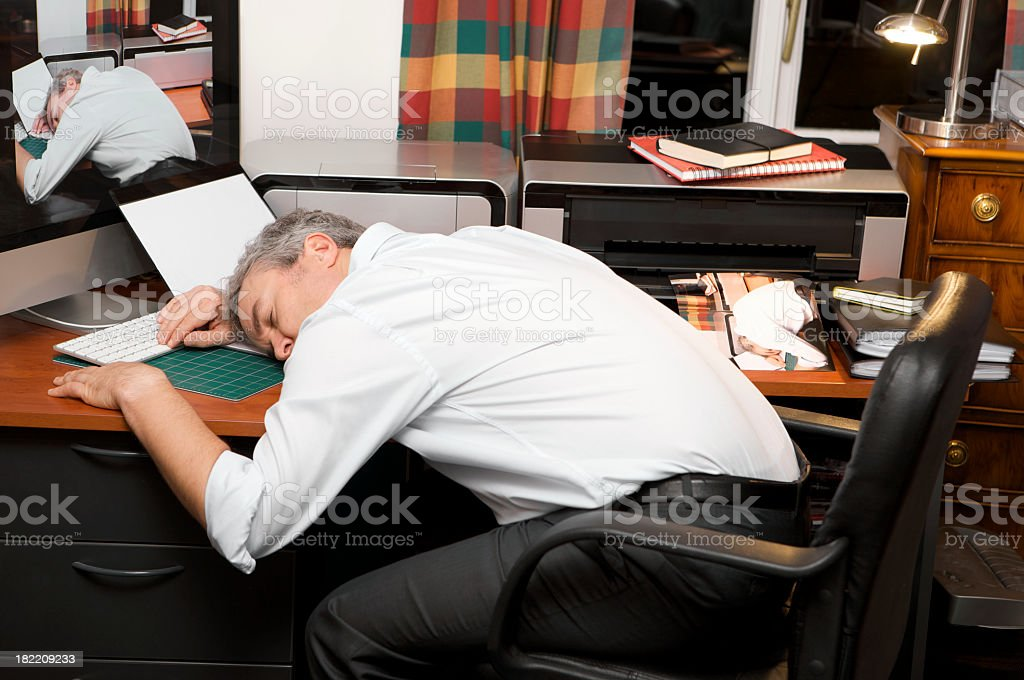 Over worked businessman asleep at home office desk at night. stock photo
