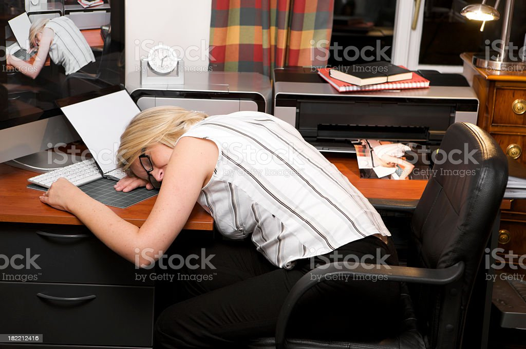 Over worked businesswoman asleep at home office desk at night. stock photo